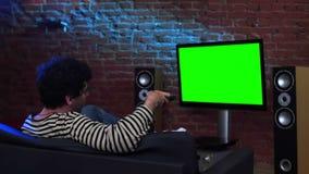 Hombre que ve la TV vía satélite con la pantalla verde almacen de metraje de vídeo