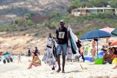 Hombre que vende la ropa en la playa Imágenes de archivo libres de regalías