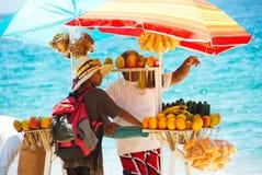 Hombre que vende los mangos en la playa imagen de archivo libre de regalías