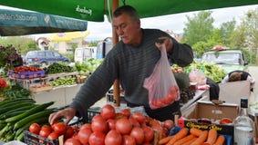 Hombre que vende verduras en el mercado Imagen de archivo