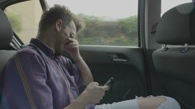 Hombre que viaja en coche en el app de la ojeada de la ciudad que birla en la pantalla táctil que mira el contenido divertido en  metrajes
