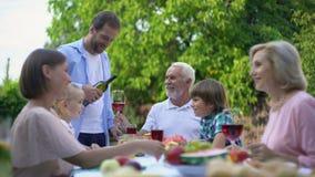 Hombre que vierte el vino envejecido costoso al padre mayor, tradiciones de la celebración de familia metrajes