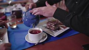 Hombre que vierte té negro en una taza almacen de metraje de vídeo