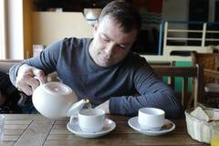 Hombre que vierte té verde imagenes de archivo