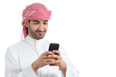 Hombre árabe del saudí que mira medios sociales en el teléfono elegante Fotografía de archivo libre de regalías