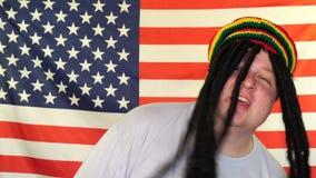 Hombre rastafarian feliz que se divierte, baile y cantando reggae en el fondo de una bandera de los E.E.U.U. almacen de video
