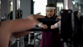 Hombre rechoncho útil que presenta en el espejo como atleta fuerte, motivación del entrenamiento fotografía de archivo