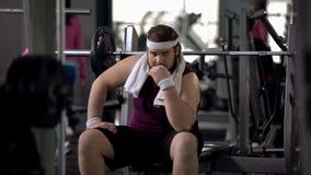 Hombre rechoncho inseguro en la sensación del gimnasio trastornado debido al exceso de peso, timidez fotos de archivo libres de regalías