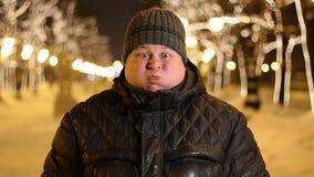 Hombre rechoncho joven que hace caras divertidas al aire libre en una noche del invierno almacen de video