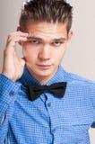 Hombre refinado en una camisa azul con la corbata de lazo negra Fotos de archivo libres de regalías