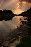 Hombre reflejado en el lago en la puesta del sol Foto de archivo