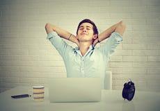 Hombre relajado con el ordenador portátil que se sienta en el fondo de la pared de ladrillo del escritorio fotos de archivo
