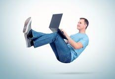 Hombre relajado en la ropa casual que trabaja en un ordenador portátil altísimo en el aire Comodidad irreal del concepto foto de archivo