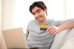 Hombre relajado joven que paga en línea con la tarjeta de crédito en sofá fotos de archivo