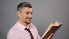 Hombre relajado que lee el libro interesante y que ríe, tiempo libre, literatura almacen de metraje de vídeo