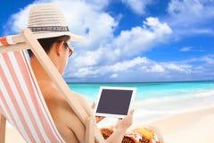 Hombre relajado que se sienta en sillas de playa y la tableta conmovedora Imágenes de archivo libres de regalías