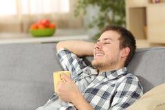 Hombre relajado que sostiene una taza de café en casa Fotografía de archivo