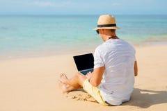 Hombre relajado que trabaja con el ordenador portátil en la playa Imagenes de archivo
