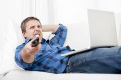 Hombre relajado que usa el ordenador en casa que enciende la TV Foto de archivo libre de regalías