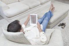 Hombre relajado que usa la tableta de Digitaces Imagen de archivo libre de regalías