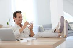 Hombre relajado que usa smartphone en casa con los pies en la tabla Foto de archivo