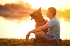 Hombre relajado y perro que disfrutan de puesta del sol o de salida del sol del verano Fotos de archivo libres de regalías