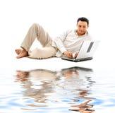 Hombre Relaxed con la computadora portátil en la arena blanca Imagen de archivo