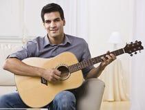 Hombre Relaxed que toca la guitarra Foto de archivo libre de regalías
