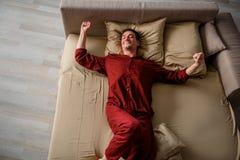 Hombre reservado que se relaja en dormitorio Fotografía de archivo