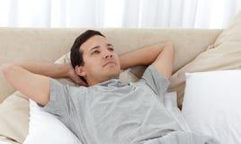 Hombre reservado que se relaja en su cama imagen de archivo