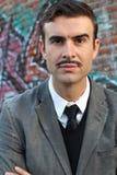 Hombre retro llamativo con el bigote sobre ciudad urbana de la manera del callejón con el fondo de la pintada Foto de archivo