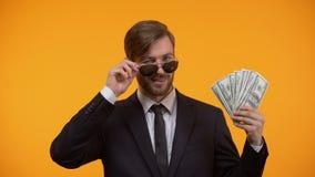 Hombre rico fresco en las gafas de sol que muestran el manojo de dólares y que guiñan, ganador de lotería metrajes