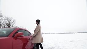 Hombre rico joven que camina en campo nevoso al coche juguetón rojo almacen de video