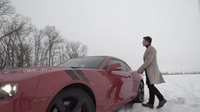 Hombre rico joven que camina en campo nevoso al coche rojo del músculo almacen de metraje de vídeo