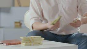 Hombre rico que cuenta dólares en las manos, poniéndolas en la tabla al lado de tacos, riqueza metrajes