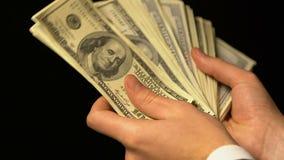 Hombre rico que cuenta efectivo del dólar, lotería o al ganador del juego del casino, concepto de la fortuna almacen de video