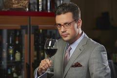Hombre rico que tuesta con el vino Foto de archivo