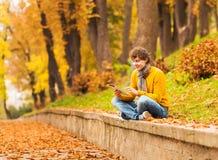 Hombre rizado con la tableta del ordenador en parque del otoño Imágenes de archivo libres de regalías