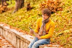 Hombre rizado en amarillo con la tableta del ordenador en otoño imagen de archivo