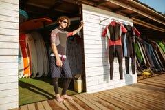 Hombre rizado en el traje de baño que se coloca en la choza de la playa Fotos de archivo