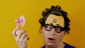 Hombre rizado graciosamente y cómico con la fan del rosa del juguete almacen de metraje de vídeo