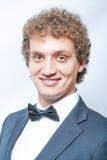 Hombre rizado sonriente en negro y corbata de lazo Fotografía de archivo