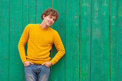 Hombre rizado sonriente en suéter amarillo en fondo de madera verde Imagen de archivo libre de regalías
