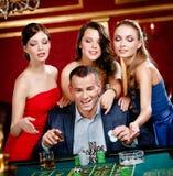 Hombre rodeado por la ruleta de los juegos de las mujeres Foto de archivo libre de regalías