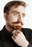 Hombre rojo joven del pelo con la barba y bigote en traje negro en el fondo blanco Foto de archivo