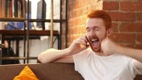 hombre rojo joven en el teléfono, oferta del pelo de las buenas noticias de trabajo de la celebración metrajes