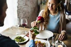 Hombre romántico que da a una Rose a la mujer una fecha fotos de archivo libres de regalías