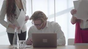 Hombre rubio acertado del retrato en los vidrios que se sientan en una oficina cómoda ligera con netbook en la firma de la tabla almacen de video