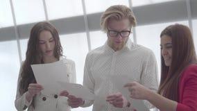 Hombre rubio acertado del retrato en vidrios que explica su idea a dos colegas femeninos que se colocan a cada lado de ?l adentro almacen de video
