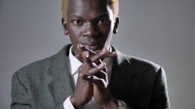 Hombre rubio afroamericano joven en el traje que lleva a cabo las manos y la rogación, mirando in camera, aislado en fondo gris almacen de metraje de vídeo